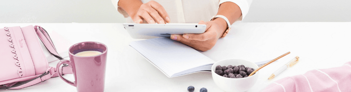 white table with a violet mug and a person holding an ipad