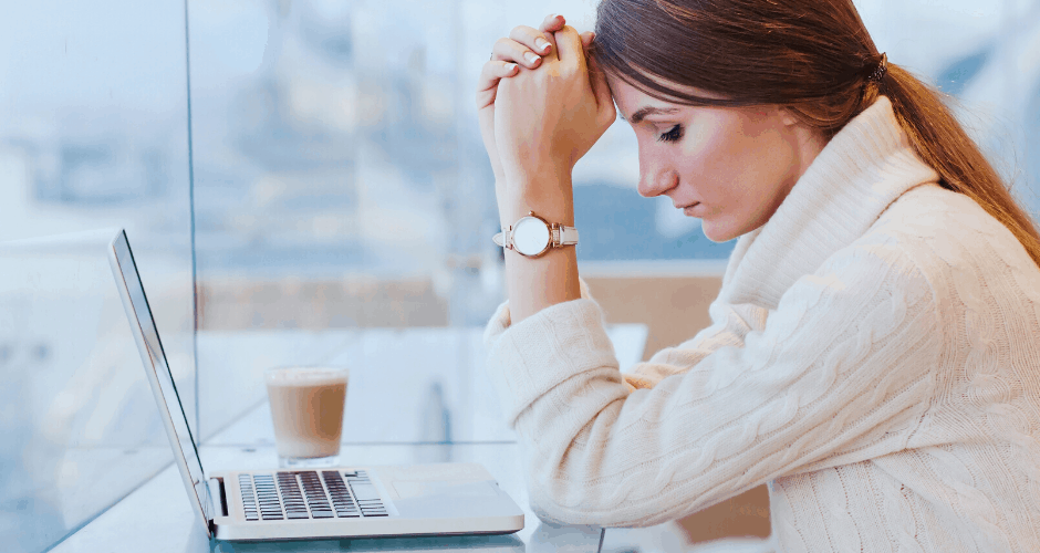 Stressed woman near laptop