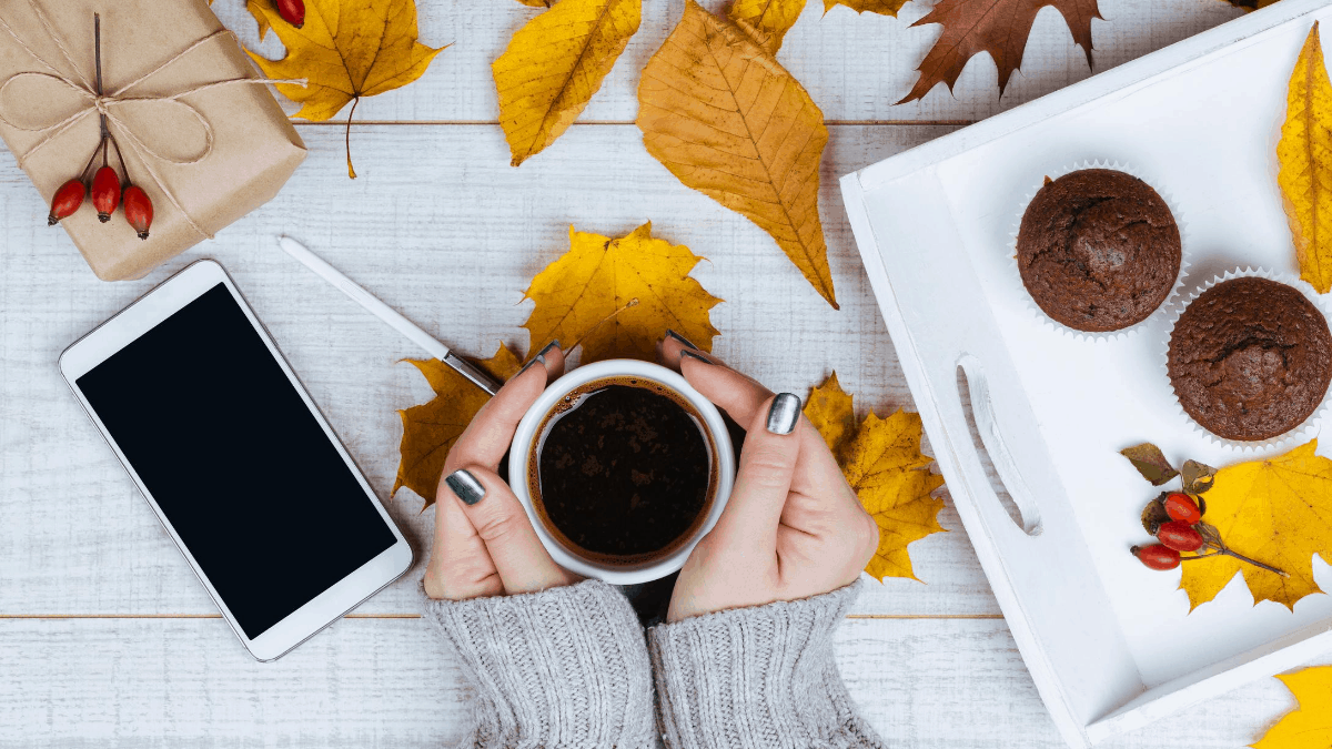 Fall Instagram captions - Women holding a cup of coffee on a home office table desk covered with fall leaves a gift and black screen smartphone