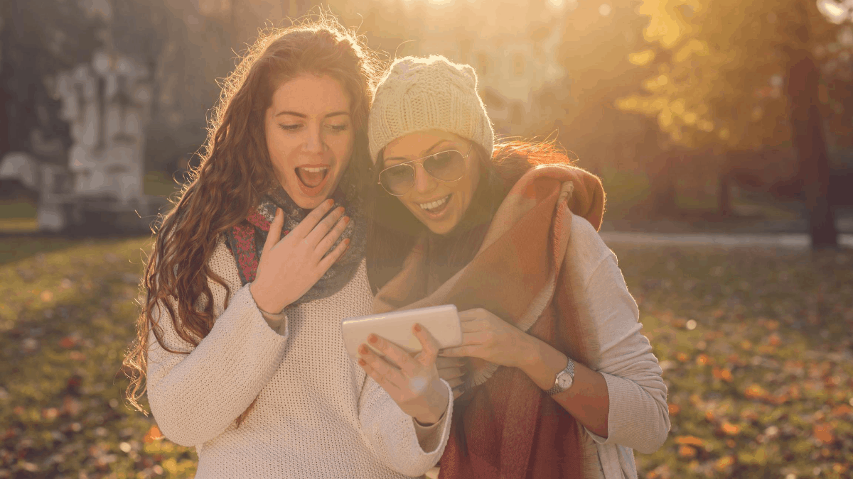 Two women laughing at funny Fall Instagram captions on smartphone