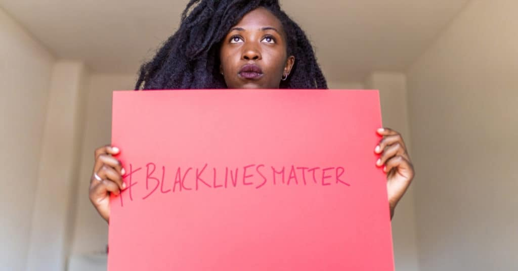 "Young black woman holding ""Black Lives Matter"" banner indoors"